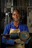 Afroamericano con la amoladora de ángulo foto de archivo