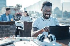 Afroamericano felice che ghigna largamente mentre usando touchpad Fotografia Stock