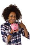 Afroamericano femminile con la banca piggy Immagini Stock Libere da Diritti