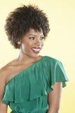Afroamericano hermoso en apagado un vestido del hombro que mira lejos sobre fondo coloreado Imagenes de archivo