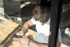 Afroamericano hermoso que mira un tel?fono m?vil en una cafeter?a imagen de archivo