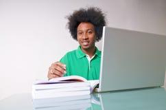 Afroamericano que estudia con la computadora portátil Foto de archivo libre de regalías
