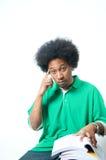 Afroamericano que piensa con el libro de textos Fotografía de archivo libre de regalías