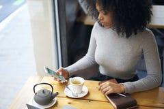 Afroamericano riccio in un rivestimento grigio che si siede in caffè facendo uso di Internet e del telefono senza fili Fotografia Stock Libera da Diritti