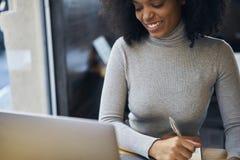 Afroamericano riccio in un rivestimento grigio e collegamento senza fili ad Internet 4G nella zona di wifi del caffè Fotografia Stock Libera da Diritti