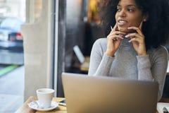 Afroamericano riccio in un rivestimento grigio e collegamento senza fili nella zona di wifi del caffè Immagine Stock Libera da Diritti