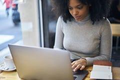 Afroamericano riccio in un rivestimento grigio facendo uso di collegamento senza fili ad Internet 4G ed al computer portatile Fotografia Stock Libera da Diritti