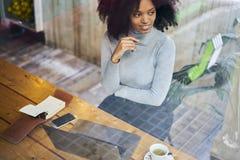 Afroamericano riccio in un rivestimento grigio facendo uso di collegamento senza fili libero ad Internet nella zona di wifi Fotografie Stock