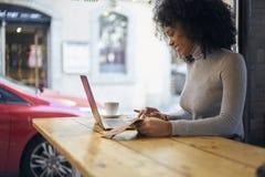 Afroamericano rizado en una chaqueta gris que envía informe financiero al empresario vía el ordenador portátil y el wifi Fotos de archivo
