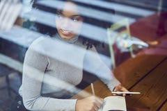 Afroamericano rizado en una chaqueta gris que sienta una tabla en cafetería Imagen de archivo libre de regalías