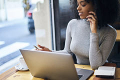 Afroamericano rizado en una chaqueta gris usando la radio libre 5G que se sienta en café Fotos de archivo libres de regalías