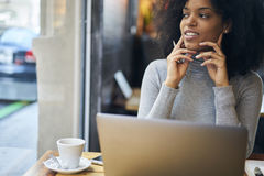 Afroamericano rizado en una chaqueta gris y conexión inalámbrica en zona del wifi del café Imagen de archivo libre de regalías