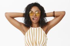Afroamericano sicuro femminile ed alla moda civettuolo femminile in occhiali da sole d'avanguardia e nel tenersi per mano superio immagini stock libere da diritti