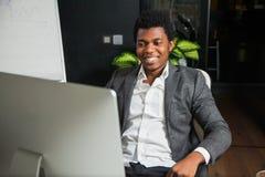 Afroamericano sorridente laborioso allo sguardo dell'ufficio al monitor del computer Fotografie Stock Libere da Diritti