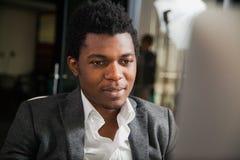 Afroamericano sorridente laborioso allo sguardo dell'ufficio al monitor del computer Immagini Stock