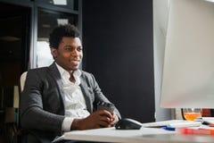 Afroamericano sorridente laborioso allo sguardo dell'ufficio al monitor del computer Fotografia Stock Libera da Diritti