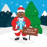 Afroamericano sveglio Santa Claus con un regalo in sue mani Paesaggio delle montagne, foresta, neve Fotografie Stock