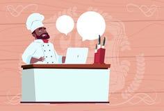 Afroamerikaner-Chef-Koch-Working At Laptop-Computer-Karikatur-Restaurant-Leiter in weißem einheitlichem Sit At Desk Over Wooden Stockbild