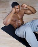 Afroamerikaner, den das Handeln sitzt, ups und knirscht Lizenzfreie Stockfotografie