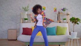 Afroamerikaner, den Frau mit einer Afrofrisur einen Smartphone benutzt, erhielt gute Nachrichten und genießt zu tanzen stock footage