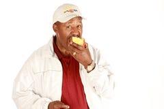 Afroamerikaner, der Apfel isst Stockbild