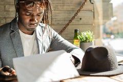 Afroamerikaner, der ein Restaurant-Men? betrachtet lizenzfreie stockfotografie