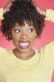 Afroamerikaner, der seitlich mit den Händen im Haar über farbigem Hintergrund schaut Lizenzfreie Stockfotografie