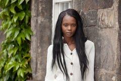 Afroamerikaner, der vor Steinwand steht lizenzfreie stockfotografie