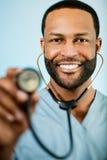 Afroamerikaner-Doktor Holding Up ein Stethoskop Lizenzfreie Stockbilder