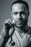 Afroamerikaner-Doktor Performing An Examination Lizenzfreie Stockfotos
