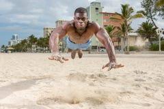 Afroamerikaner-Eignungs-Modellliegestütz auf dem Strand Lizenzfreie Stockbilder
