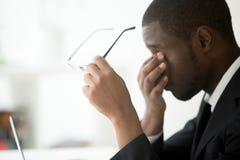 Afroamerikaner ermüdete die Geschäftsmanngefühls-Augenermüdung, die O nimmt lizenzfreie stockfotografie