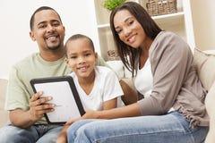 Afroamerikaner-Familie unter Verwendung des Tablette-Computers Stockfotos