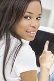Afroamerikaner-Frau auf Tablette-Computer zu Hause stockbild