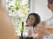Afroamerikaner-Frau, die bei Tisch lächelt Stockfotografie