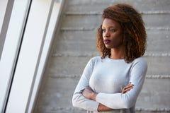 Afroamerikaner-Geschäftsfrau-Standing Against Office-Wand Stockfoto