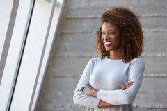 Afroamerikaner-Geschäftsfrau-Standing Against Office-Wand Lizenzfreie Stockbilder