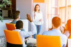 Afroamerikaner-Geschäftsleute, die dort oben Hand bei einer Konferenz anheben, um eine Frage zu beantworten stockfotos