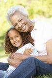 Afroamerikaner-Großmutter und Enkelin, die im Park sich entspannen lizenzfreies stockfoto