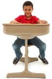 Afroamerikaner-Junge, der in einem Schreibtisch sitzt stockfotos