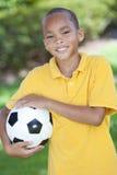 Afroamerikaner-Junge, der mit Fußball spielt Stockfotos