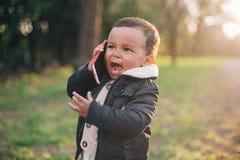 Afroamerikaner-Junge, der mit Handy spielt Lizenzfreie Stockfotos