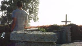 Afroamerikaner-junger Mann betrachtet hölzernes Kreuz auf Abhang bei Sonnenuntergang stock footage
