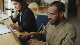 Afroamerikaner konzentrierte den Mann, der auf die Laptop-Computer schreibt, die an Softwareentwicklung im Dachbodenbüro mit Frau stock video