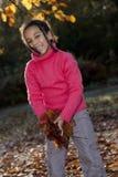 Afroamerikaner-Mädchen, das mit Fall-Blättern spielt Stockbild