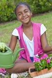 Afroamerikaner-Mädchen-Kind, das mit Blumen im Garten arbeitet Lizenzfreie Stockfotos
