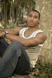 Afroamerikaner-männliches Lehnen auf Baum Lizenzfreie Stockfotografie