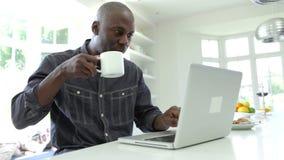 Afroamerikaner-Mann, der zu Hause Laptop verwendet stock footage