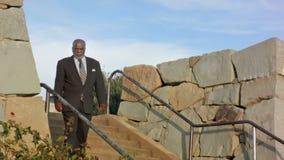 Afroamerikaner-Mann geht hinunter Steinschritte, schaut über Park stock video footage