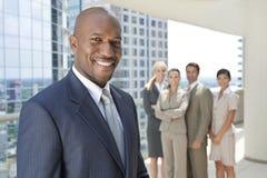 Afroamerikaner-Mann-Geschäftsmann u. Geschäfts-Team